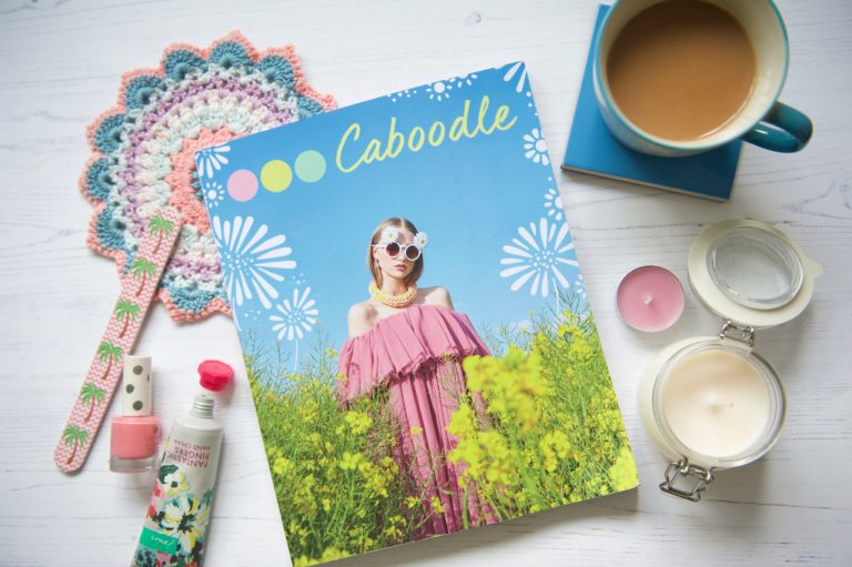 Caboodle Magazine flatlay of front cover with tea, candle, nail polish and hand cream