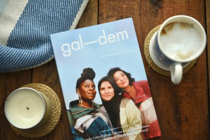 Gal-dem UN/REST magazine issue on wooden table with candle, coffee cup and blanket